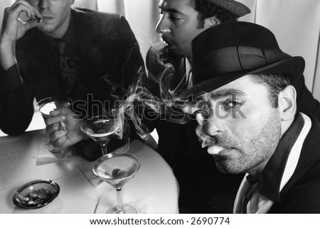 Three Caucasian prime adult males in retro suits sitting at table drinking cocktails.