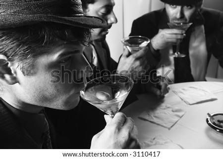 Three Caucasian prime adult males in retro suits sitting at table drinking cocktails. - stock photo