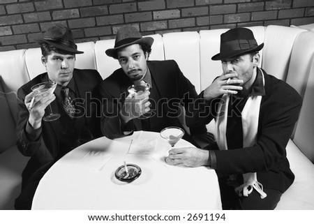 Three Caucasian prime adult males in retro suits sitting at table with cocktails looking at viewer. - stock photo