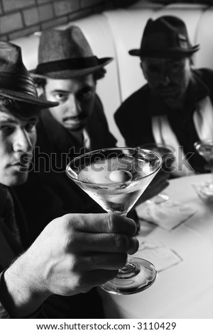 Three Caucasian prime adult males in retro suits sitting at table with martini. - stock photo