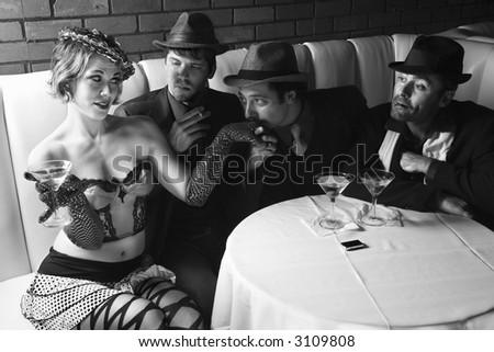 Three Caucasian prime adult males in retro suits wooing Caucasian prime adult female. - stock photo