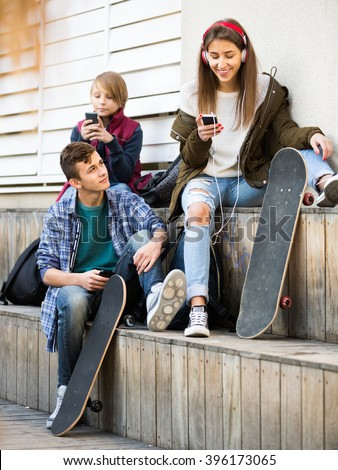 Three caucasian teenagers with smartphones in autumn day outdoors - stock photo