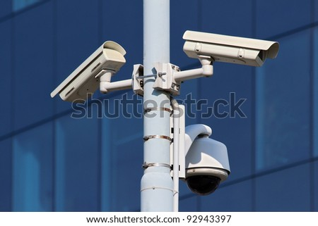 three cctv security cameras on street pylon - stock photo