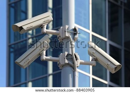 three cctv security cameras on the street pylon - stock photo