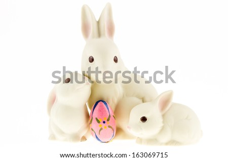 Three ceramic bunnies isolated on a white background with an Easter egg. - stock photo