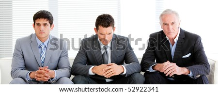 Three charismatic businessmen sitting on a sofa in a waiting room - stock photo