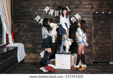 Three charming girls playing with Christmas toys - stock photo