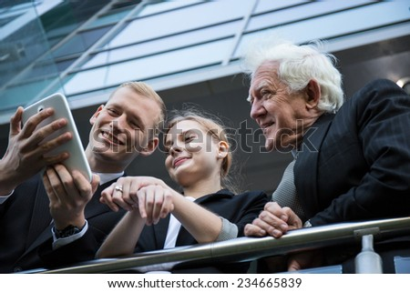 Three cheerful architects having good time during break - stock photo
