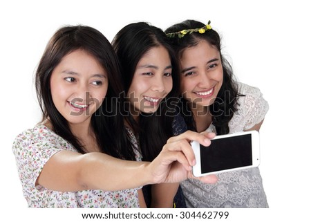Three cheerful Asian girls taking a self shot picture with smartphone, isolated on white background - stock photo