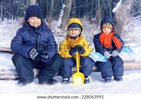 Three cheerful boy playing in a park in winter - stock photo