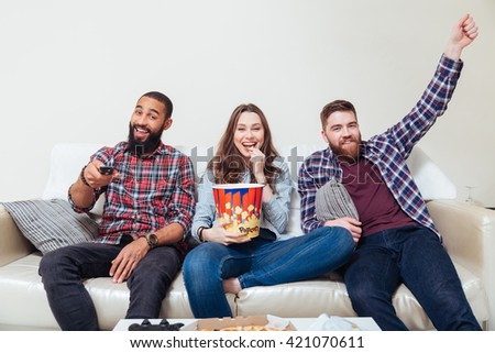 Three cheerful friends eating popcorn and watching tv together