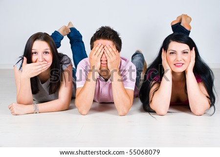 Three cheerful friends lying down on wooden floor and gesturing speak,see and hear no evil - stock photo