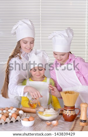 Three cheerful girls baking a cake in the kitchen together
