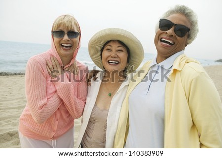 Three cheerful multiethnic female friends laughing on the beach - stock photo