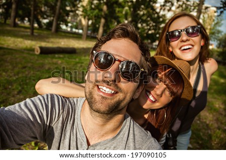 Three Cheerful People Making A Self Portrait - stock photo