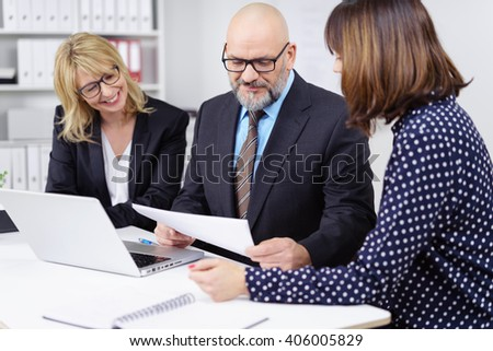 Three cheerful professional workers meeting and discussing topics on paper while seated at white table with laptop computer - stock photo