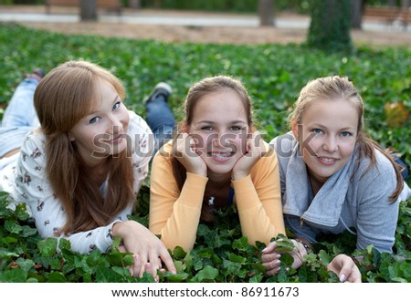 three cheerful student girls laying on the grass