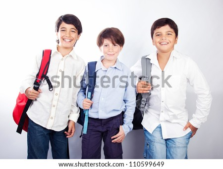 Three cheerful teenagers isolated on white background, back to school, best friends classmates, preteens standing and smiling  with backpacks and textbooks, knowledge and education concept - stock photo