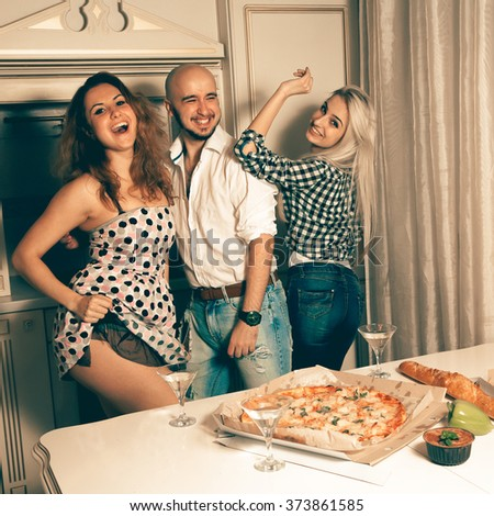 Three cheerful young people having fun at a party with alcohol and pizza. Celebrate, disco, party, nightlife, entertainment, friendship concept. - stock photo