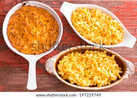 Three cheese macaroni in different clay pots on rustic table served hot - stock photo