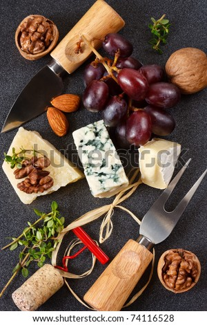 Three cheeses, almonds, walnut and grapes on a black background.
