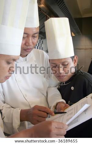 three chef discuss about menu - stock photo