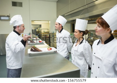 Three chefs presenting their dessert plates to the head chef in busy kitchen - stock photo