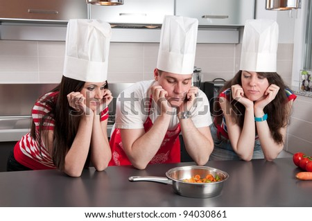 Three chefs with their elbows on the kitchen countertop staring at a pan of carrots with long faces. - stock photo