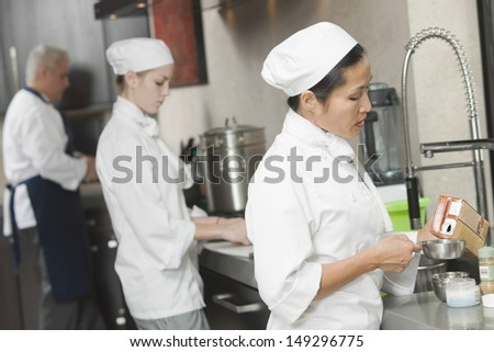 Three chefs working side by side in busy commercial kitchen - stock photo