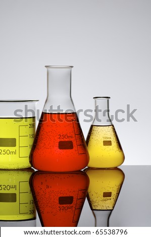 three chemical beakers with colored liquid and a white background - stock photo