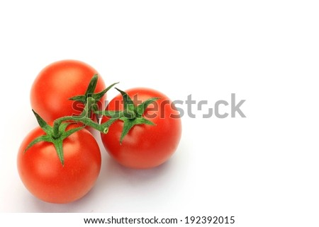 Three cherry tomatoes in a bright red color and green vines. - stock photo