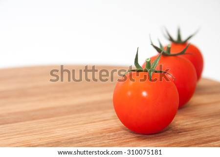 Three cherry tomatoes on the kitchen wooden board.