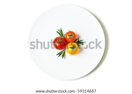 three cherry tomatoes with rosemary on a white plate isolated on white - stock photo