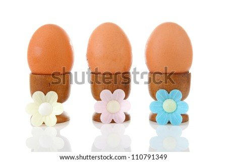 Three chicken eggs in wooden holder over white background