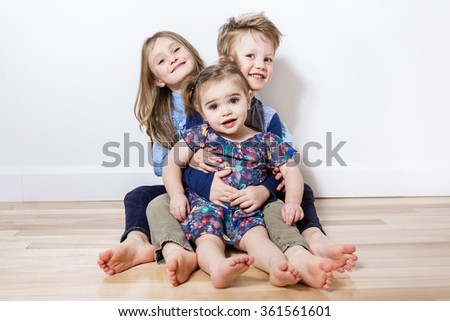 three child sit on the floor at home