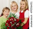 Three children - all girls - waiting with a bunch of roses for their mother, to give the flowers for birthday or mothers's day - stock photo