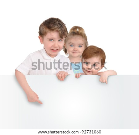 Three children are holding a blank, white signboard. They are isolated and there is a baby. Use it for an education or advertising concept.