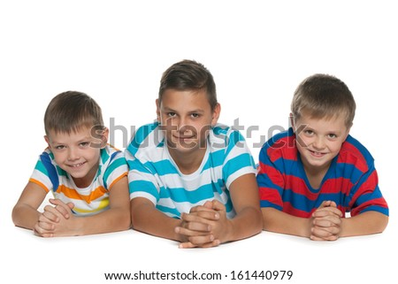 Three children are lying on the floor on a white background