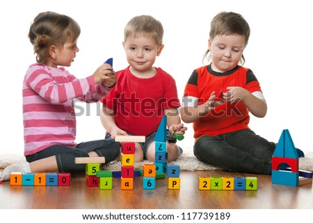 Three children are playing on the floor together - stock photo