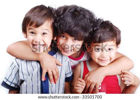 Three children are standing and smiling together