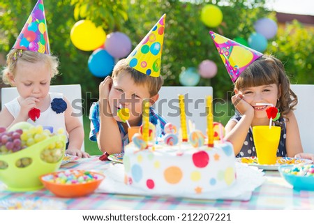 Three children celebrating birthday at outdoor party - stock photo