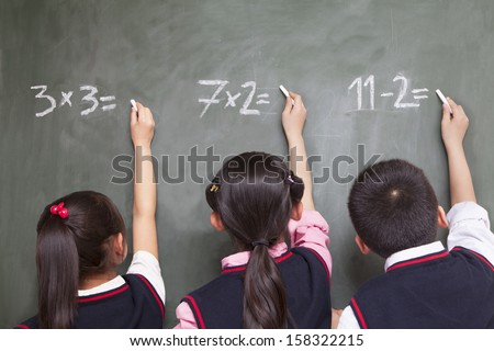 Three children doing math equations on blackboard - stock photo