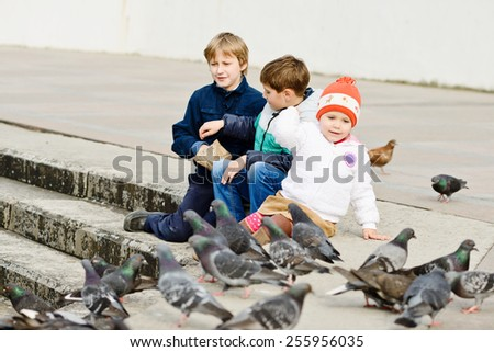 three children feeding doves in the city