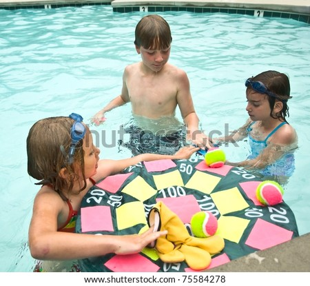 Three children getting ready to play a game in the swimming pool. - stock photo