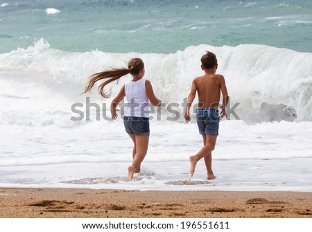Three children having an awesome time running along the beach - stock photo