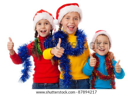 Three children in Santa hats showing thumb up sign, isolated on white