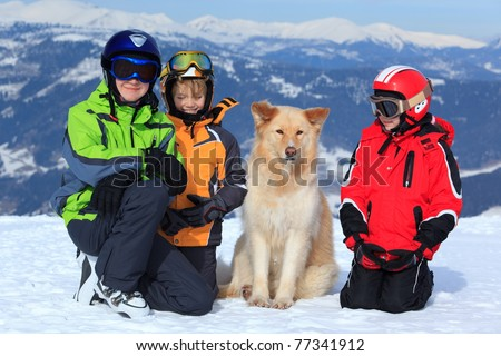Three children in ski clothing on snowy Alpine mountain with pet dog.