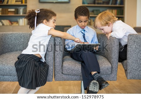 Three children in suits sits in chairs and girl shows a finger on the tablet, focus on the boy on the right.