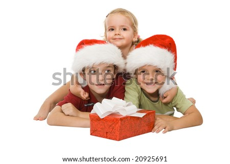 Three children laying on the floor in santa hats and hugging happy at christmas time - stock photo