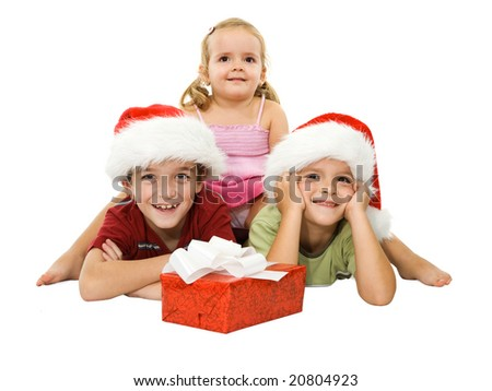Three children laying on the floor in santa hats and smiling happy at christmas time - stock photo